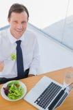 Overheadkosten van een glimlachende zakenman die een salade eten Stock Afbeeldingen