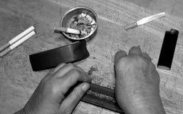 Overheadkosten van handen die sigaretten rollen Royalty-vrije Stock Afbeeldingen