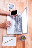 Overheadkosten van vrouwelijke handen die laptop en smartphone gebruiken Royalty-vrije Stock Afbeeldingen
