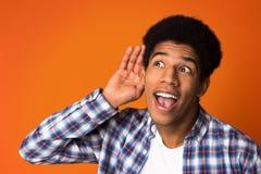 Overhear conversation. Guy holding hand near ear. Over orange background stock photos