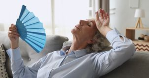 Overheated exhausted old woman feel hot wave fan on sofa