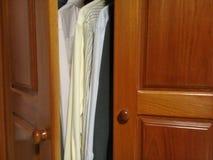 Overhemden in de houten kast met goed licht stock afbeelding