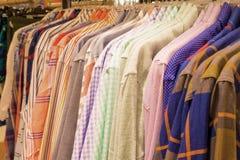 Overhemden op hangers in kledingsopslag, voorraad, sasle stock fotografie