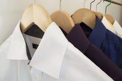 Overhemden op houten hangers Stock Afbeeldingen