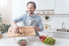 Overjoyed adult man cooking vegetable salad Royalty Free Stock Images