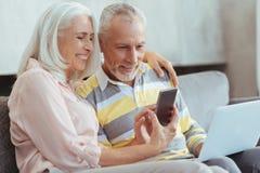Overjoyed aged couple using modern devices stock photo