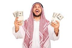 Overjoyed Arab holding stacks of money Royalty Free Stock Photography