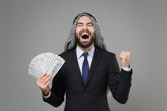 Overjoyed arabian muslim businessman in keffiyeh kafiya ring igal agal black suit isolated on gray background