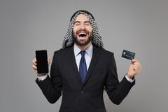 Overjoyed arabian muslim businessman in keffiyeh kafiya ring igal agal suit  on gray background. Achievement