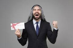 Overjoyed bearded arabian muslim businessman in keffiyeh kafiya ring igal agal suit isolated on gray background