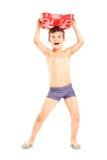 Overjoyed boy holding a swimming float. Full length portrait of an overjoyed boy holding a swimming float isolated on white background royalty free stock photos