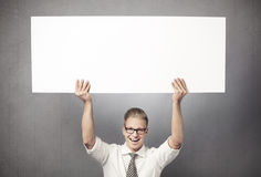 Overjoyed businessman holding empty horizontal  panel. Royalty Free Stock Photos
