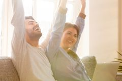 Overjoyed couple celebrating online betting bid win sitting on couch. Happy overjoyed couple celebrating online betting bid lottery win sitting on couch with royalty free stock photography