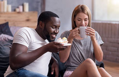 Overjoyed couple drinking tea with cupcakes in bedroom Stock Photos