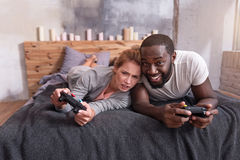 Overjoyed couple enjoying video games in bed. Sweet family times. Overjoyed young international couple enjoying video games and using console while lying in bed Royalty Free Stock Photos