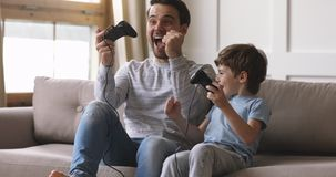 Overjoyed dad and child son gamers winners playing winning videogame