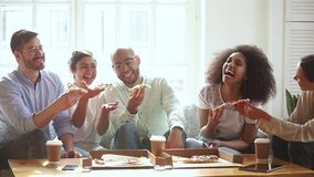 Overjoyed cheerful diverse friends gather together eating pizza enjoy conversation
