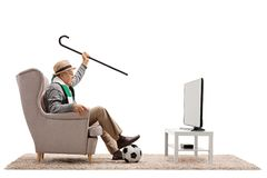 Overjoyed elderly soccer fan with a scarf and cane watching tele. Overjoyed elderly soccer fan with a scarf and cane seated in an armchair watching television Royalty Free Stock Photo