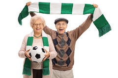 Overjoyed elderly soccer fans with a football and a scarf Stock Photos