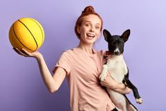 Overjoyed excited ginger girl teaching her dog to play with a ball