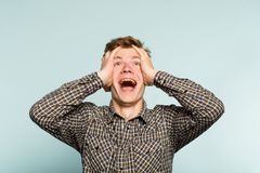 Overjoyed happy excited man clutching head emotion. Overjoyed extremely happy and excited man clutching his head. portrait of a young guy on light background royalty free stock photo