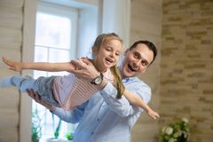 Overjoyed father and daughter playing on weekend at home. Little girl happy flying like plane in air at daddy hands spending time together, laughing, smiling royalty free stock images