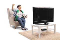 Overjoyed female soccer fan seated in an armchair watching footb. All on TV isolated on white background Royalty Free Stock Photography