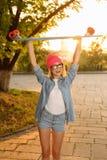 Overjoyed girl holding skateboard Stock Images