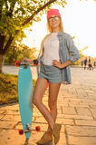 Overjoyed girl holding skateboard Stock Image