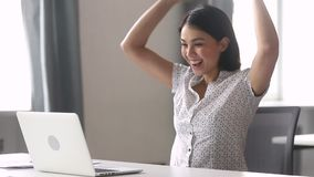 Overjoyed happy asian business woman winner looking at laptop computer