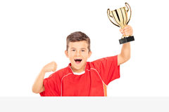 Overjoyed kid holding a trophy behind a panel Royalty Free Stock Images