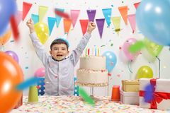 Overjoyed kid with a party hat and birthday cake Stock Photo