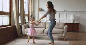 Overjoyed little child dancing twisting with mother.
