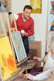 Overjoyed man teaching people in painting studio. Stock Photography