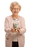 Overjoyed mature woman holding a jar filled with money Stock Photo