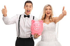 Overjoyed newlyweds holding a piggybank and giving thumbs up Royalty Free Stock Images