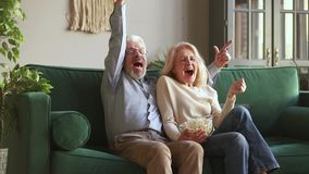Overjoyed old mature couple football fans watching sport tv game