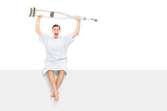 Overjoyed patient raising his crutches in the air. Overjoyed male patient raising his crutches in the air seated on a panel isolated on white background Stock Image