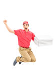 Overjoyed pizza delivery guy jumping Stock Photos