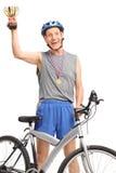 Overjoyed senior cyclist holding a golden trophy Stock Photos