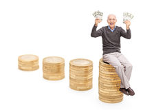 Overjoyed senior holding money seated on stack of coins Royalty Free Stock Images