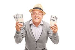 Overjoyed senior holding two stacks of money stock photos
