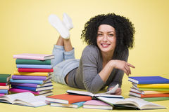 Overjoyed smiling student girl reading surrounded by colorful bo Stock Photos