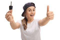 Overjoyed teenage girl holding car key and thumb up Stock Image