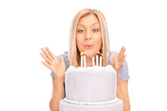 Overjoyed woman blowing candles on a cake Stock Photo