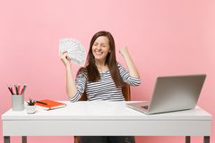 Overjoyed woman clenching fists like winner holding bundle lots of dollars, cash money work at office at white desk with. Pc laptop isolated on pink background stock images