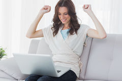 Overjoyed woman looking at her laptop Royalty Free Stock Photo