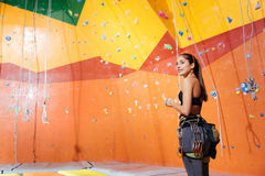 Overjoyed woman preparing to climb up the wall royalty free stock photo