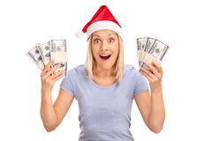Overjoyed woman with Santa hat holding money Royalty Free Stock Photo