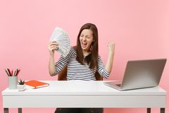Overjoyed woman screaming clenching fists like winner holding bundle lots of dollars, cash money work at white desk with. Pc laptop isolated on pink background royalty free stock photos